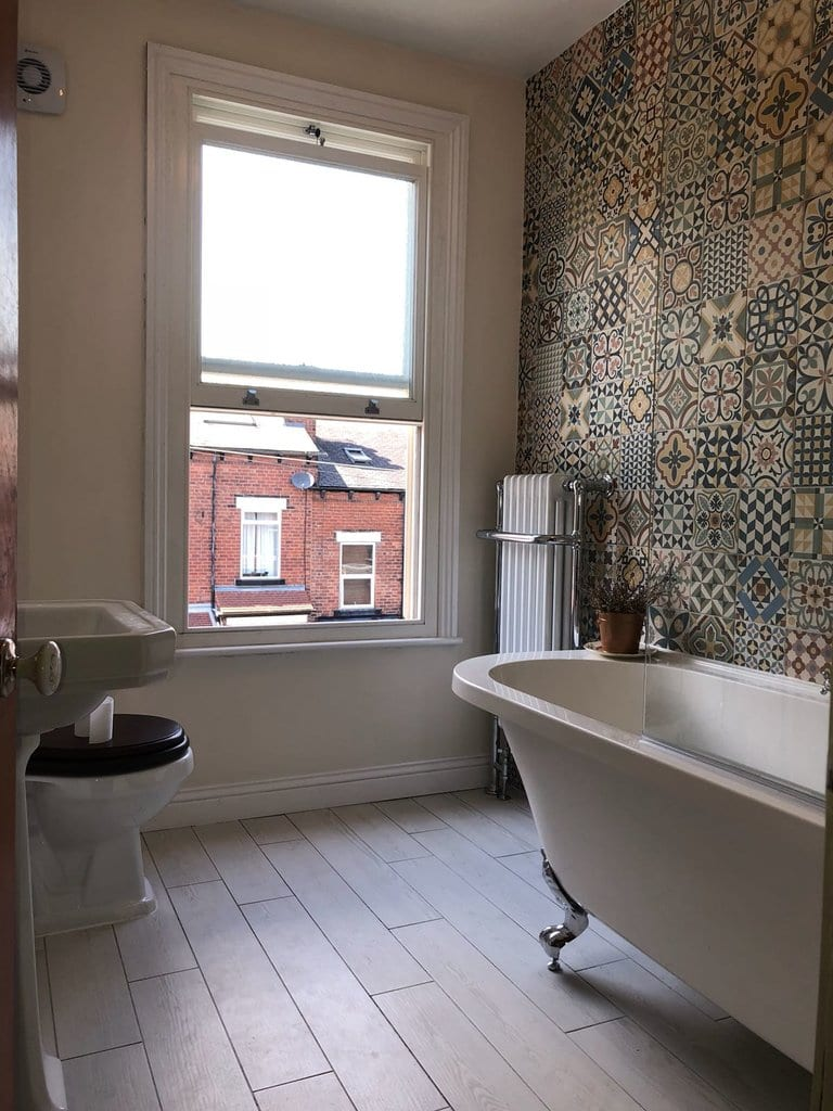 Bathroom fitted with a bath and shower by a plumber in Leeds with nice tiles