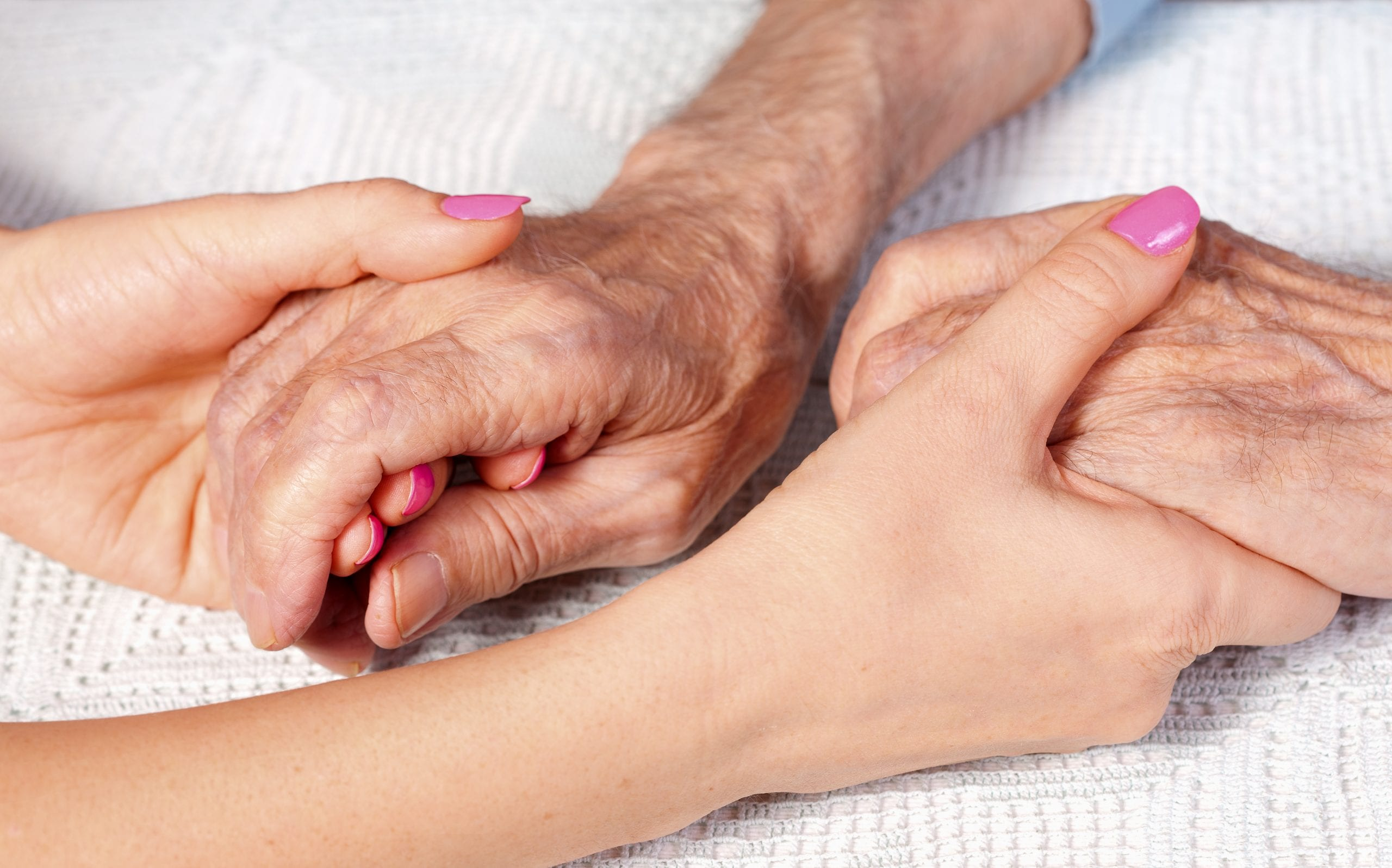 Young and old person hold hands at care home