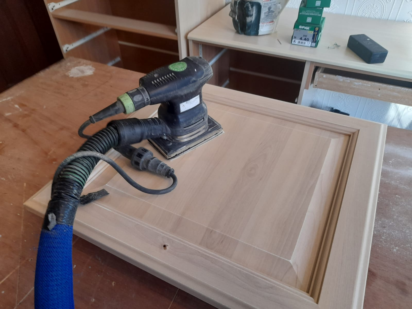 Photo of a decorators professional 99% dust free sander being used to sand down a kitchen cabinet ready for the kitchen to be hand painted