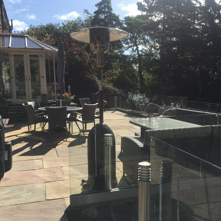 beautiful back garden patio with glass border and seating area in Denby Dale, Duddersfield